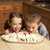 two kids excited over banana split