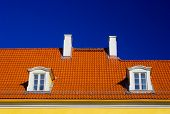 stock photo of gabled dormer window  - Orange roof with two windows and chimneys against blue sky - JPG