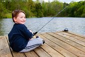Boy smiles while fishing from dock on lake.
