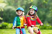 Kids Ride Balance Bike In Park poster