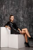 Young Girl Sits On White Cube, In Studio, Model In Black Leather Dress And Sneakers. Gray Shabby Bac poster