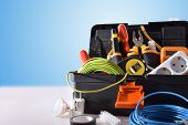 Toolbox Full Of Tools And Electrical Equipment On White Table And Blue Isolated Background. Front Vi poster