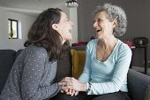 Elderly Woman And Daughter Laughing And Holding Hands. Mother And Daughter Sitting On Couch With Hom poster