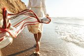 Portrait of positive girl 20s walking with waving scarf along seashore poster