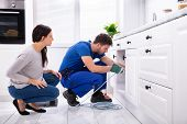 Woman Looking At Male Plumber Cleaning Clogged Sink Pipe With Drained Cable In Kitchen poster