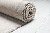 Rolled Fuzzy Carpet On Wooden Background, Closeup. Space For Text poster