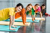 Cheerful Kids Doing Plank Exercise And Looking At Camera poster