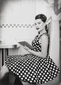 Retro (vintage) Portrait Of The Cute Young Woman Sitting In Cafe With Book. Pin Up Style Portrait Of poster
