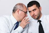 Mature businessman whisper something to his younger colleague, privacy, secret concept