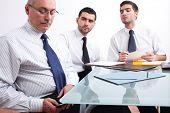 Empresário de três, um madura mensagens de texto usando seu telefone celular e dois jovens sentados à mesa dur