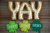 Yay Gold Lettering Word With Lucky Shamrocks, Concept For St Patricks Day In March. Flatlay On Wood  poster