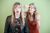 stock photo of inappropriate  - Frustrated mother behind angry daughter in provocative clothing - JPG