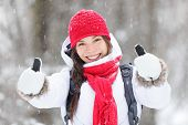 Happy young Asian woman with a beautiful vivacious smile dressed warmly in winter clothes standing outdoors in a snowstorm giving thumbs up gesture of approval