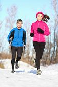 Young couple running dressed warmly in fleeces and gloves jogging in sunshine across winter snow in