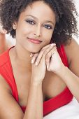 A beautiful mixed race African American girl or young woman laying down wearing a red dress