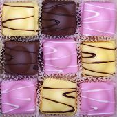 A checkerboard of fancy fondant cakes in pink, yellow and brown.