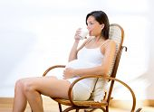Beautiful pregnant woman drinking milk at home on rocker chair