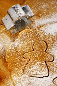 gingerbread girl cookie cutter from above with dough on wood