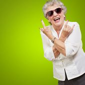 Senior woman wearing sunglasses doing funky action isolated on green background