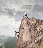 Businessman on the top of a rock helping an other businessman to climb it