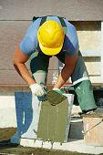 mason worker tiler making stairway from granite stone marble tile blocks