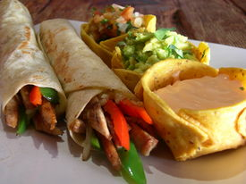 pic of mexican food  - Hot chicken burritos with pico de gallo jalapeno refried beans guacamole and cheese sauce in a mexican restaurant - JPG