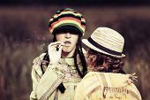 Young rastafarian people against autumn nature background