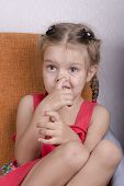 Girl sitting on the couch and picks his nose