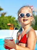 Child drinking soft drink near swimming pool.