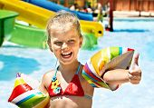 Child with armbands playing in swimming pool. Summer outdoor.