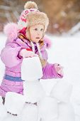 Portrait of little girl who builds wall of snow blocks in winter park