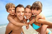 stock photo of piggyback ride  - Portrait of happy family at the beach - JPG