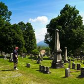 stock photo of revolutionary war  - A man looks at the cemetery of the First Church of Old Bennington Vermont whose gravestones are from the Revolutionary War - JPG