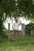 Thoughtful man standing across field gate under the tree