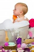 picture of soapy  - Cute little blond girl sitting in a rustic metal bathtub having a relaxing bubble bath full of soapy bubbles surrounded by luxury bathing accessories washing herself - JPG