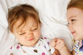 stock photo of slumber party  - Silly baby in sheets with big sister - JPG