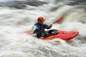 Side view of a blurred man kayaking in rough river