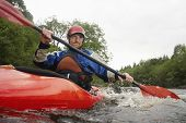 stock photo of watersports  - Low angle view of a young man kayaking in river - JPG