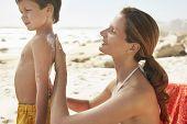 Mãe de vista lado aplicar protetor solar creme do filho na praia
