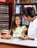 Young female librarian and schoolgirl looking at each other while sitting with books at table in library