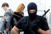 stock photo of shoplifting  - Portrait of man wearing black balaclava with gun looking at camera on background of scared business people - JPG