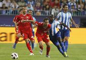 MALAGA, SPAIN. 19/09/2010. Ivica Dragutinovic a Sevilla defender and Quincy Owusu-Abeyie the Malaga