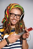 Portrait of a happy rastafarian young man playing his guitar.