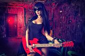 stock photo of bosom  - Beautiful sexy girl playing electric guitar in the old garage - JPG