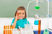 cute elementary schoolgirl at the lab holding a tube with liquid