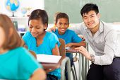 portrait of happy primary teacher helping student in classroom