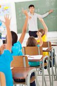 chinese language teacher in classroom pointing students who raised hands during lesson
