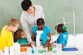 primary teacher and students in science class with young girl using microscope