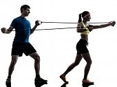 one  woman exercising resistance  rubber band fitness workout with man coach in silhouette  on white