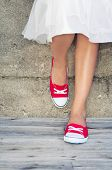Girl wearing red sneakers leaning on the wall